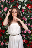 Girl in white dress posing on floral background Royalty Free Stock Photo