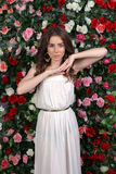 Girl in white dress posing on floral background Stock Image