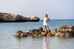 Girl in white dress posing on rocks. Young girl in white dress posing on rocks Royalty Free Stock Images