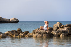 Girl in white dress posing on rocks. Young girl in white dress posing on rocks Stock Image