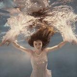 Girl in dress posing underwater