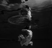 Girl in white dress posing under water with the boat Royalty Free Stock Photo