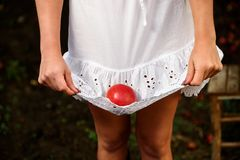 Girl with white dress and red apple. In orherd Royalty Free Stock Photos