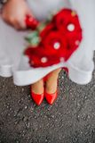 Girl in white dress with red bouquet stock images