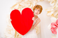 Girl in white dress with red heart in hands. Girl in white dress on background of paper flowers with red heart in hands Stock Images