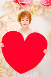 Girl in white dress with red heart in hands Royalty Free Stock Images