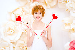 Girl in white dress with red heart in hands. Girl in white dress on background of paper flowers with red heart in hands Stock Photo