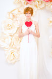 Girl in white dress with red heart in hands. Girl in white dress on background of paper flowers with red heart in hands Stock Photos