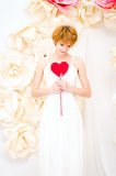 Girl in white dress with red heart in hands. Girl in white dress on background of paper flowers with red heart in hands Royalty Free Stock Images