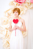 Girl in white dress with red heart in hands. Girl in white dress on background of paper flowers with red heart in hands Royalty Free Stock Image