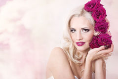 Girl in a white dress with roses. In her hair Royalty Free Stock Image