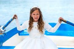 Girl in white dress rowing on lake. Stock Photo
