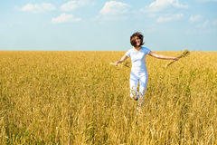 Girl in a white dress running on field. Stock Image