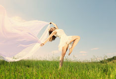 Spring Girl. The girl in a white dress runs on a grass Royalty Free Stock Photography