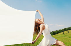 Spring Girl. The girl in a white dress runs on a grass Stock Photos