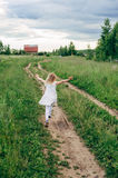 Child runs and jumps on a path in the field Stock Photos