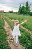 Child runs and jumps on a path in the field Stock Images