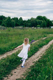 Child runs and jumps on a path in the field Royalty Free Stock Photo