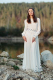 A girl in a white dress on the shore of a pond Royalty Free Stock Photo