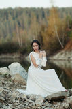 A girl in a white dress on the shore of a pond Royalty Free Stock Photos