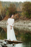 A girl in a white dress on the shore of a pond Royalty Free Stock Photography
