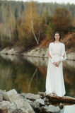 A girl in a white dress on the shore of a pond Royalty Free Stock Images