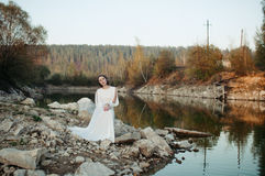 A girl in a white dress on the shore of a pond Stock Photo