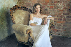 Girl in white dress sit in vintage chair. Beautiful teen girl in white dress sit in vintage chair Stock Images