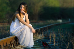 Girl in white dress sitting barefoot on the railroad. Stand next to the shoes. Stock Photos
