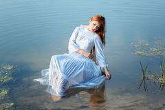 Girl white dress sitting on chair in a lake. Royalty Free Stock Photography