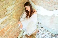 Girl in white dress sitting in the corner Stock Photo