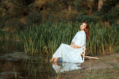 Girl white dress sitting dipping feet in the lake. Stock Photo