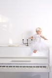 A girl in white dress sitting on a piano Royalty Free Stock Photos