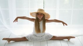 Girl in a white dress sitting on a white floor in a straw hat. On a twine stock video footage
