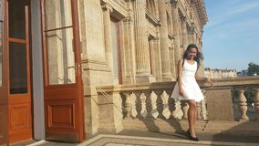 Girl in white dress. Smiling Papuan girl - young woman dressed in white dress standing on balcony of National Theater in Prague, Czech Republic stock video