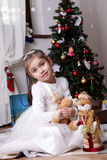 Girl in white dress with snowman under Christmas tree Stock Photography