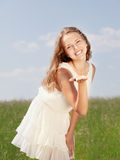 Spring Girl. The girl in a white dress stand on a green grass stock image