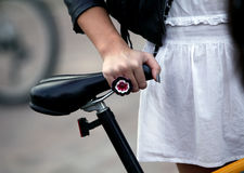 Girl in a white dress with standing near the bike Royalty Free Stock Photos