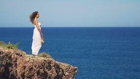 Girl in a white dress is standing on a rock cliff. a woman looks out into the distance on an endless sea surface.  stock video footage