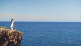 Girl in a white dress is standing on a rock cliff. a woman looks out into the distance on an endless sea surface.  stock video