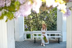 A girl in a white dress and a straw hat is enjoying the flowering of wisteria. royalty free stock photos