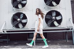 Girl in white dress and striped socks walking on the street. Streetstyle, fashion. Girl in white dress and striped socks walking on the street. Propellers on Stock Photos