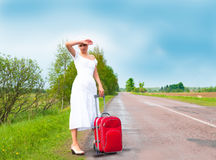 Girl in white dress with suitcase on road Royalty Free Stock Images