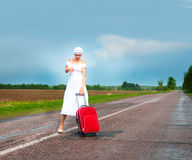 Girl in white dress with suitcase on road Stock Photography