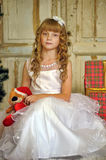 Girl in white dress with a toy bear sits stock photography