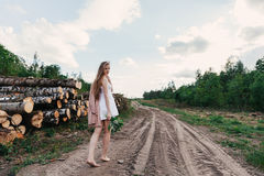 Girl in white dress in the village goes on the road Royalty Free Stock Photo