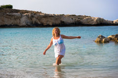 Girl in white dress walking in sea. Attractive blond hair girl in white dress walking in sea Royalty Free Stock Photography