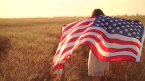 Girl in white dress wearing an American flag while running in a beautiful wheat field