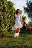 A girl in a white dress with a white hat in her hand and whitewash a cat at her feet watching the sunset. A girl in a white dress with a bouquet of white flowers Royalty Free Stock Photography