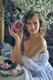 Girl in a white evening dress with a flower in the hands Stock Images